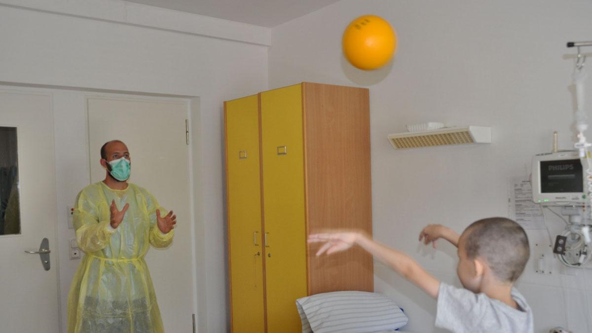 Sportwissenschaftler Dominik Gaser spielt Ball mit jungem Krebspatienten (Foto: S. Kesting)