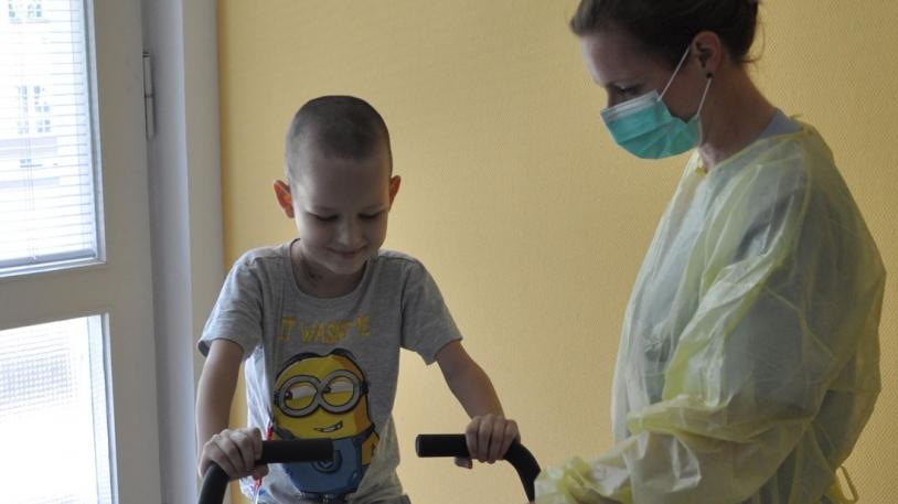 Dr. Sabine Kesting mit jungem Krebspatienten auf Ergometer