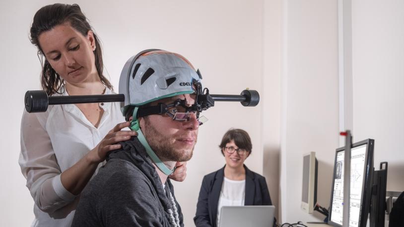 Dr. Cecilia Ramaioli (links) überprüft den Sitz des Helms mit Gewichten bei einem Probanden. Prof. Nadine Lehnen stellt im Hintergrund den Rechner für das Experiment ein