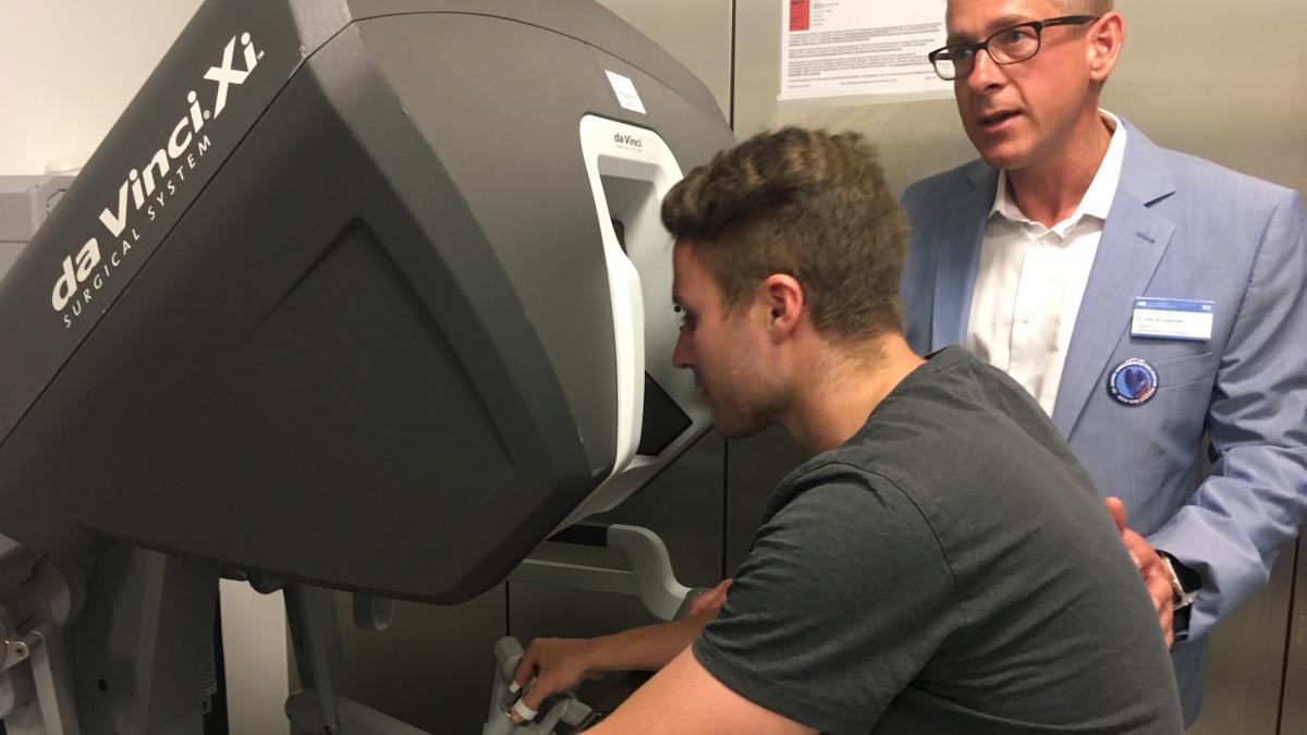 Simon an der Konsole des Da Vinci OP-Roboters mit Oberarzt Dr. Michael Autenrieth