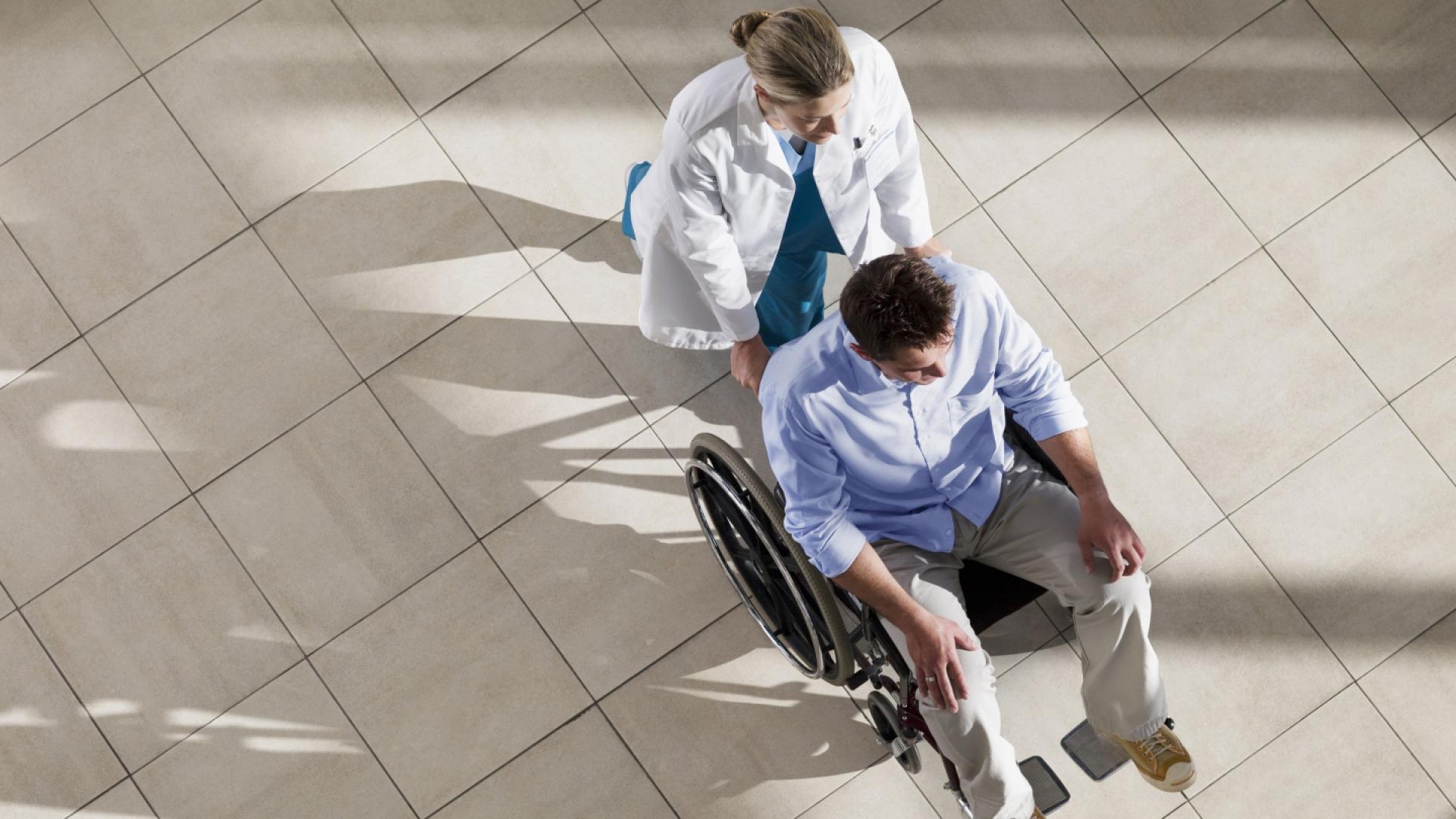 Ärztin schiebt Patient im Rollstuhl