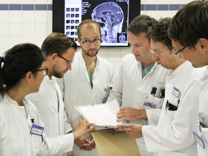 Fallbesprechung im Behandlungsraum mit CT-Bild auf dem Monitor