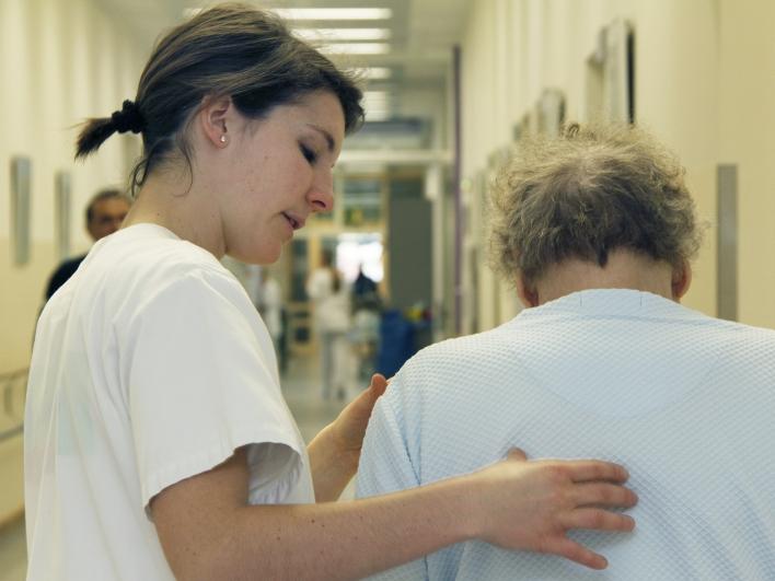 Krankenpflegerin mit Patientin im Gang