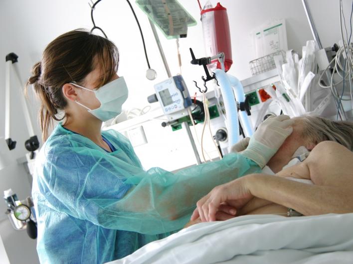 Krankenpflegerin mit Mundschutz bei Patientin